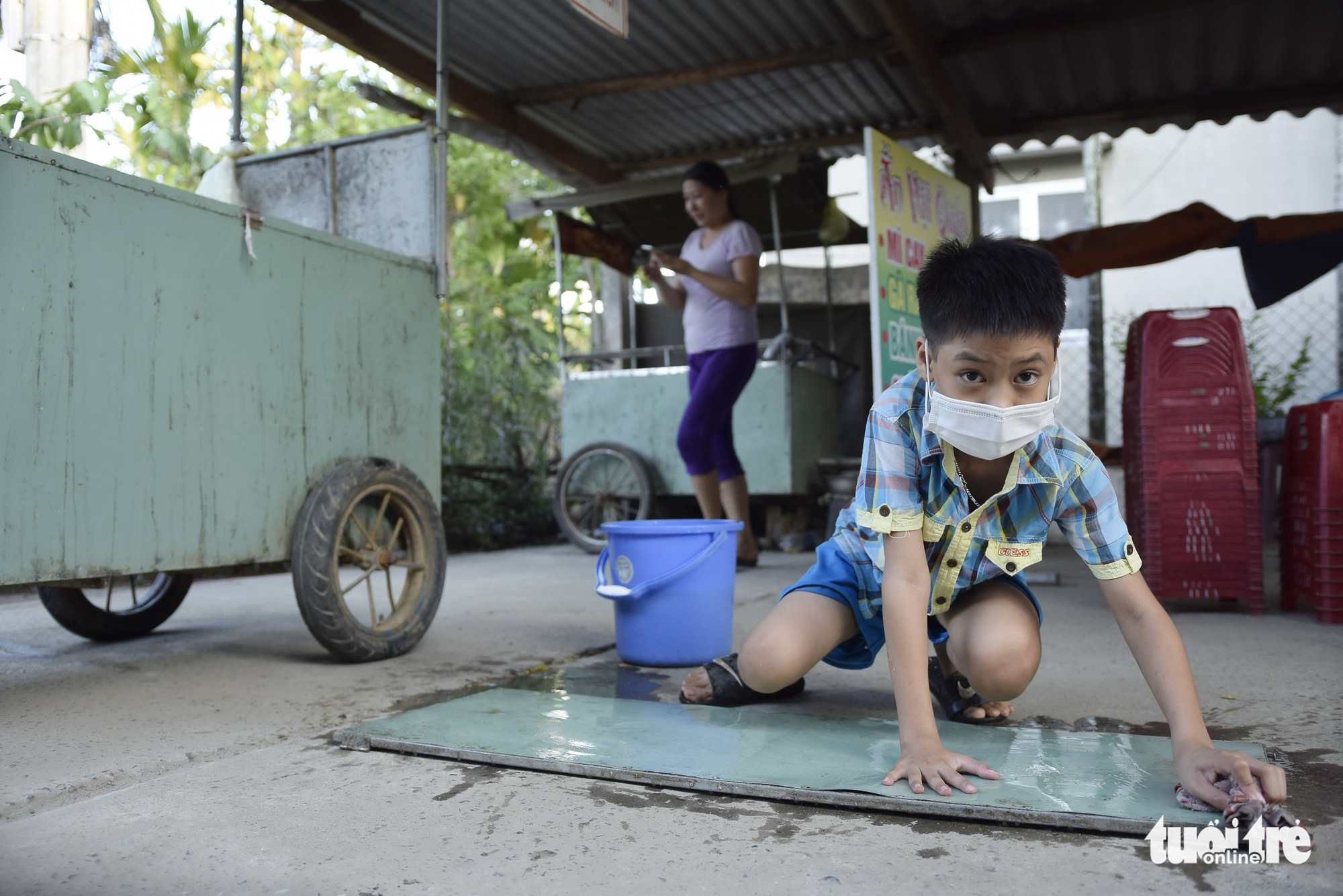 Nguyen Ngoc Thien Thanh helps clean things so that his grandmother and mother can get their food cart back on track in Hoi An City, Quang Nam Province in central Vietnam following a pandemic-caused disruption in this supplied photo.