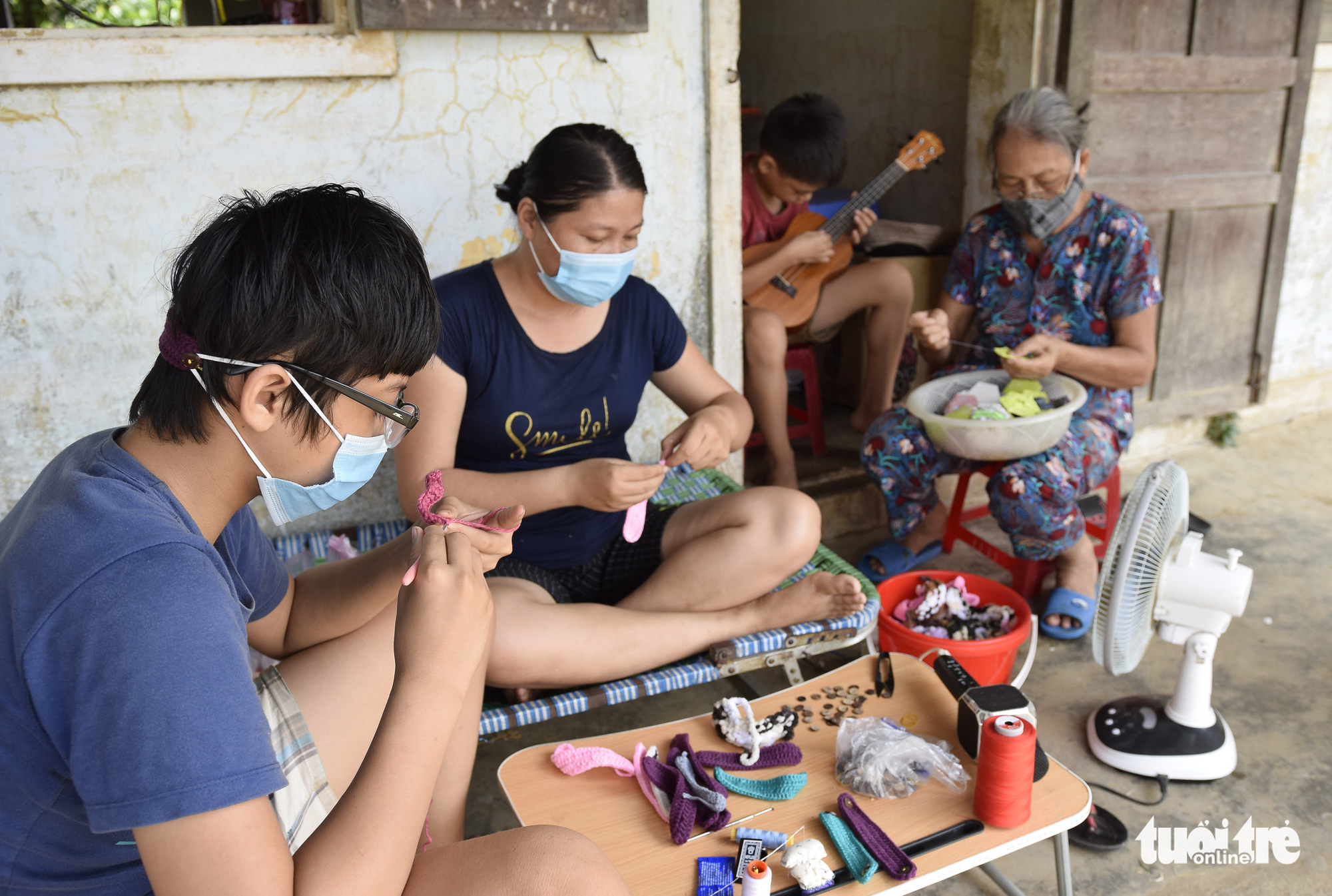 Nguyen Tuong Van (second left), her mother and two sons knit cushions that relieve mask wearers of discomfort in this supplied photo. The family donated more than 300 knitted cushions to frontliners during the lockdown in place to curb the second coronavirus disease (COVID-19) outbreak that hit Da Nang City in central Vietnam and neighboring Quang Nam Province in July 2020.