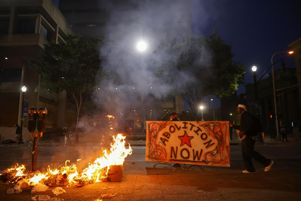 rotesters carry a sign as they walk by a fire in front of the Louis D. Brandeis Hall of Justice after a grand jury voted to indict one of three white police officers for wanton endangerment in the death of Breonna Taylor, who was shot dead by police in her apartment, in Louisville, Kentucky, U.S. September 23, 2020. Photo: Reuters