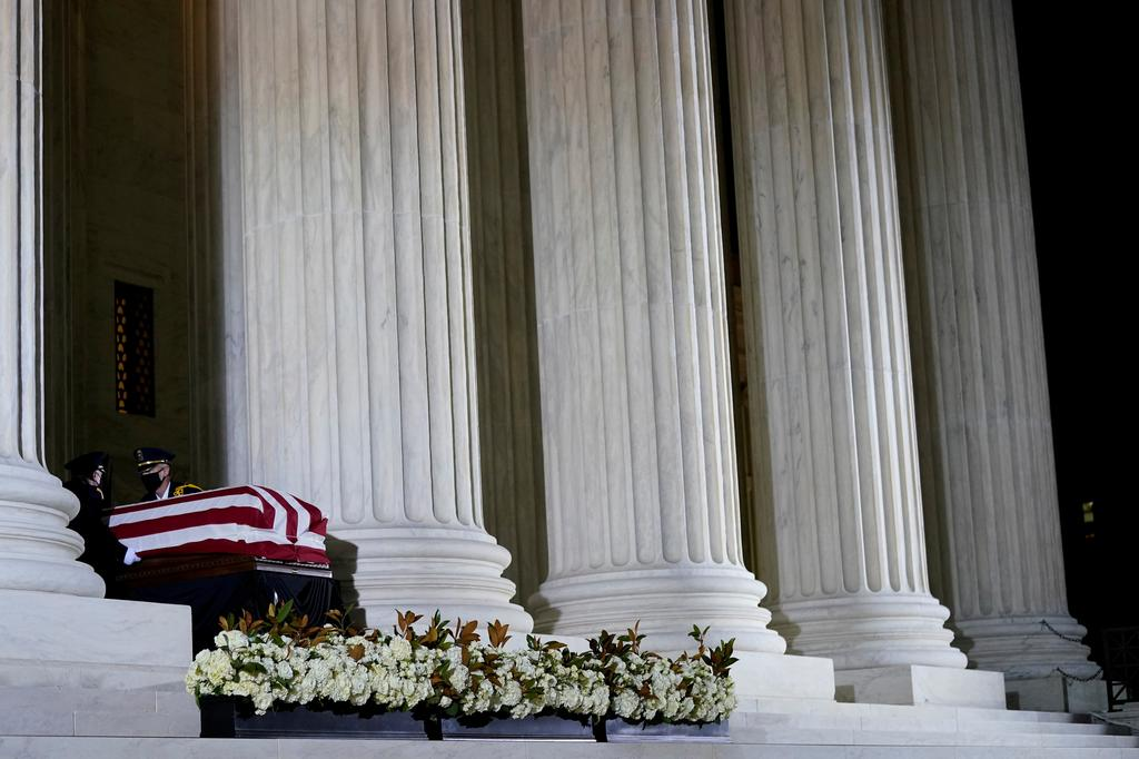 A Supreme Court Honor Guard salutes before moving the flag-draped casket of Justice Ruth Bader Ginsburg back into the court as Ginsburg lies in repose under the Portico at the top of the front steps of the U.S. Supreme Court building in Washington, U.S., September 24, 2020. Photo: Reuters