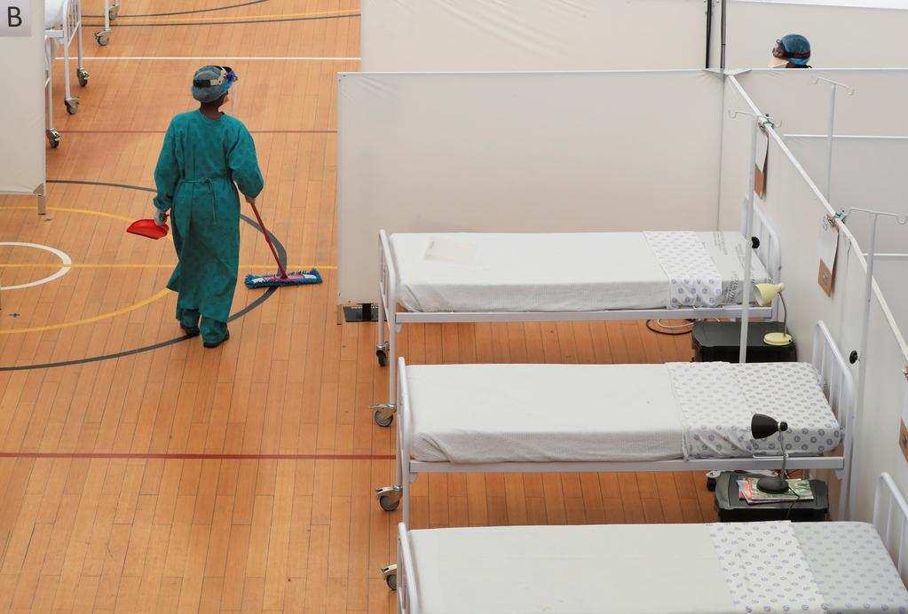 A health worker walks between beds at a temporary field hospital set up in a sports complex by Medecins Sans Frontieres (MSF) during the coronavirus disease (COVID-19) outbreak in Khayelitsha township near Cape Town, South Africa, July 21, 2020. Photo: Reuters