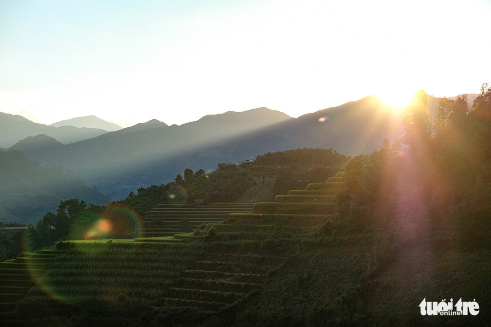 The sun goes down behind the mountains casting long shadows on terraced fields in Mu Cang Chai District, Yen Bai Province, Vietnam. Photo: Nam Tran / Tuoi Tre