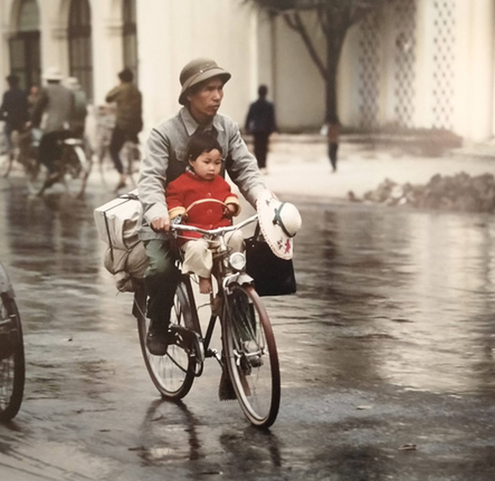 A man carries a baby on a bicycle in Hanoi in this photo taken by German photographer Thomas Billhardt during the 1970s.