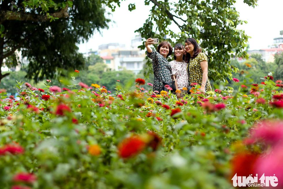 Hanoi residents selfie near a newly-planted flower corner next to Hoan Kiem Lake. Photo: Nguyen Khanh / Tuoi Tre