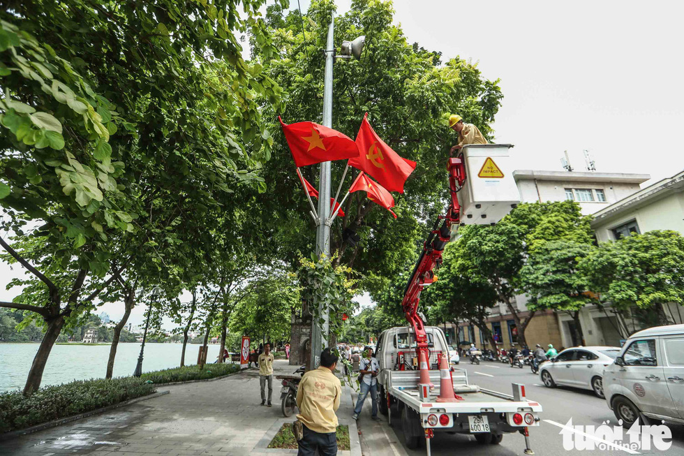 Workers are seen hanging flags in celebration of Hanoi's 1010th anniversary in this photo taken at the Hoan Kiem Lake. Photo: Nguyen Khanh / Tuoi Tre