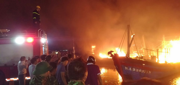 Onlookers watch fishing boats on fire at Lach Quen fishing port, located in Quynh Luu District in Nghe An Province, Vietnam, October 9, 2020. Photo: Ngoc Tuan / Tuoi Tre