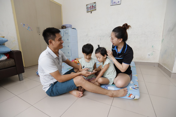 Dao Van Han, a lecturer at the VNU - Ho Chi Minh City, and his wife Dang Thi Tuyet An, a planning and finance officer at the University of Economics and Law in the VNU - Ho Chi Minh City, play with their twin children at a 35-square-meter apartment at the university's public housing complex. Photo: Nhu Hung / Tuoi Tre