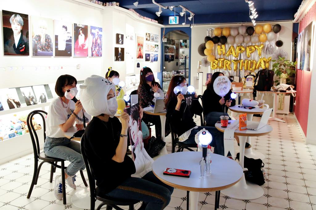 Fans of K-pop idol boy band BTS enjoy as they watch a live streaming online concert, wearing a protective masks to avoid the spread of the coronavirus disease (COVID-19), at a cafe in Seoul, South Korea October 10, 2020. Photo: Reuters