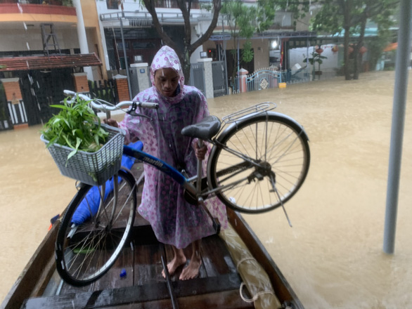 A resident of Hoi An City load a bicycle onto a boat in this photo taken on Sunday. Photo: B.D. / Tuoi Tre