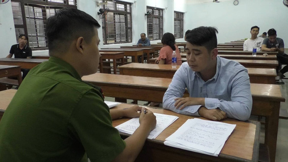 A police officer interviews a suspect in the largest-ever online football betting ring in Da Nang City, Vietnam, October 13, 2020. Photo: A.B. / Tuoi Tre