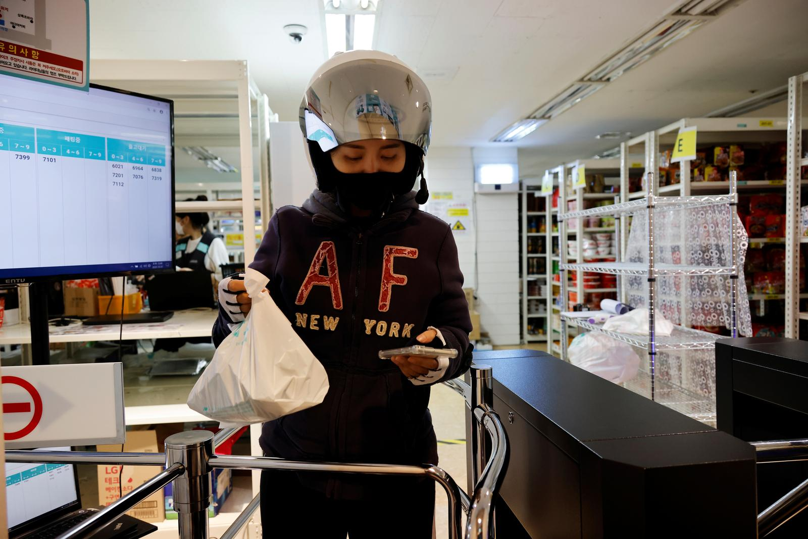 Chey Young-ah, a dispatch rider, checks her mobile phone while delivering groceries in Seongnam, South Korea, October 7, 2020. Photo: Reuters