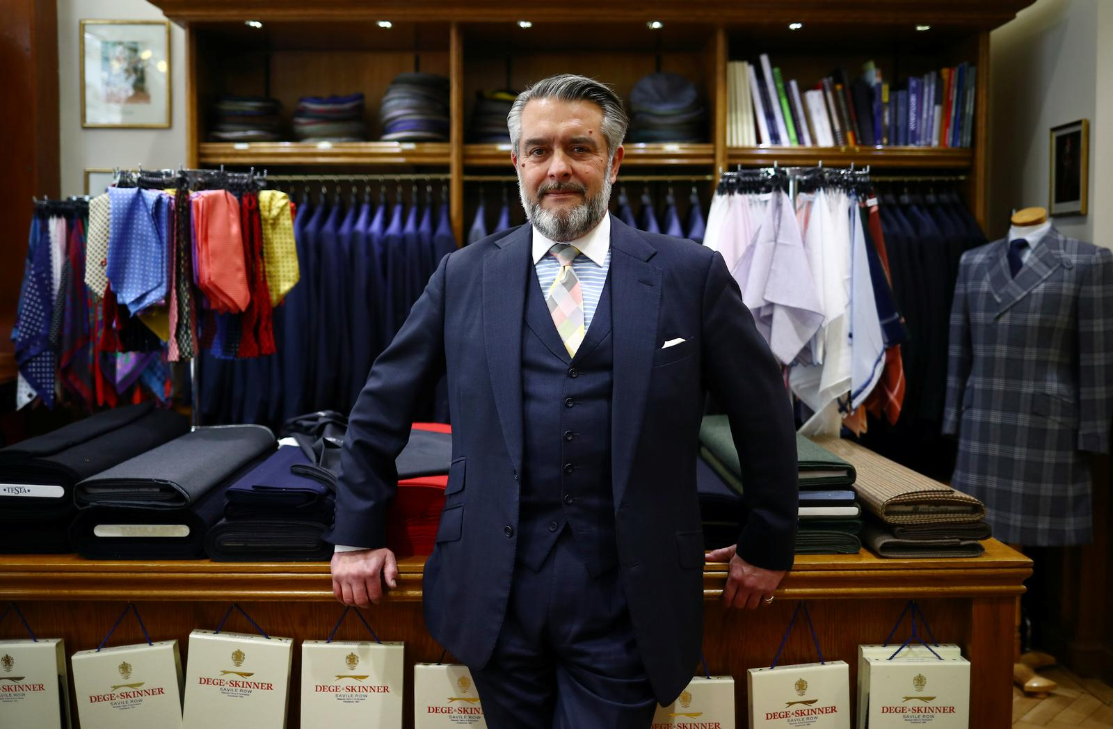 """Dege & Skinner Managing Director William Skinner poses for a portrait in the Dege & Skinner tailors on Savile Row, amid the coronavirus disease (COVID-19) outbreak, in London, Britain October 7, 2020. William Skinner is a fifth-generation tailor and the third to run the Savile Row shop Dege & Skinner. Established in 1865, Dege & Skinner is one of only two family-owned Savile Row firms. Its clients include businessmen, generals and royals including Prince Harry, who chose the brand for his wedding uniform. Business has been """"quite challenging,"""" but since reopening in June, the shop has seen """"quite a lot"""" of new customers. """"It's been on their bucket list for a long time,"""" Skinner said about some of his new customers, who think: """"if I get COVID, then I might never do this, so let's do it now'."""" """"There's a whole raft of attitudes out there … feedback we've had from some of our clients is 'we've had nothing to spend our money on over the last 3-6 months, so I'm going to buy a new suit'."""" Nevertheless, orders for the past six months are about one-quarter of what they would normally be. The company usually makes about 500-600 suits a year, starting at £5,500 each. Picture taken October 7, 2020. Photo: Reuters"""