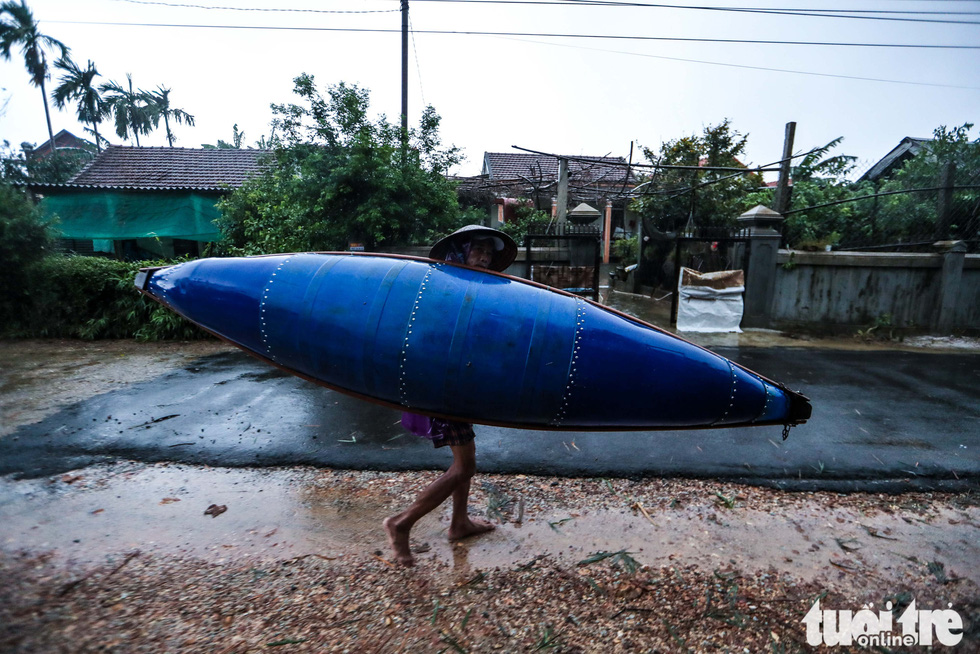 A man carries a boat on his shoulder on the way home before flooding in Thua Thien-Hue Province, October 16, 2020. Photo: Nguyen Khanh / Tuoi Tre