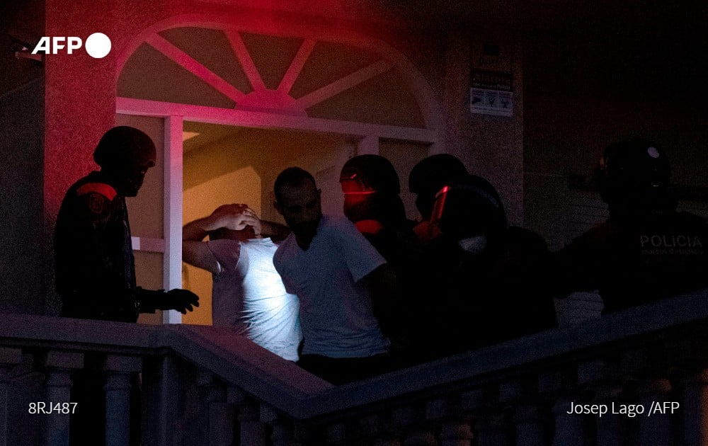 Members of the Catalan regional police force Mossos d'Esquadra arrest two men during an intervention in an illegal marijuana plantation in a private residence in Martorell near Barcelona on October 6, 2020. Photo: AFP
