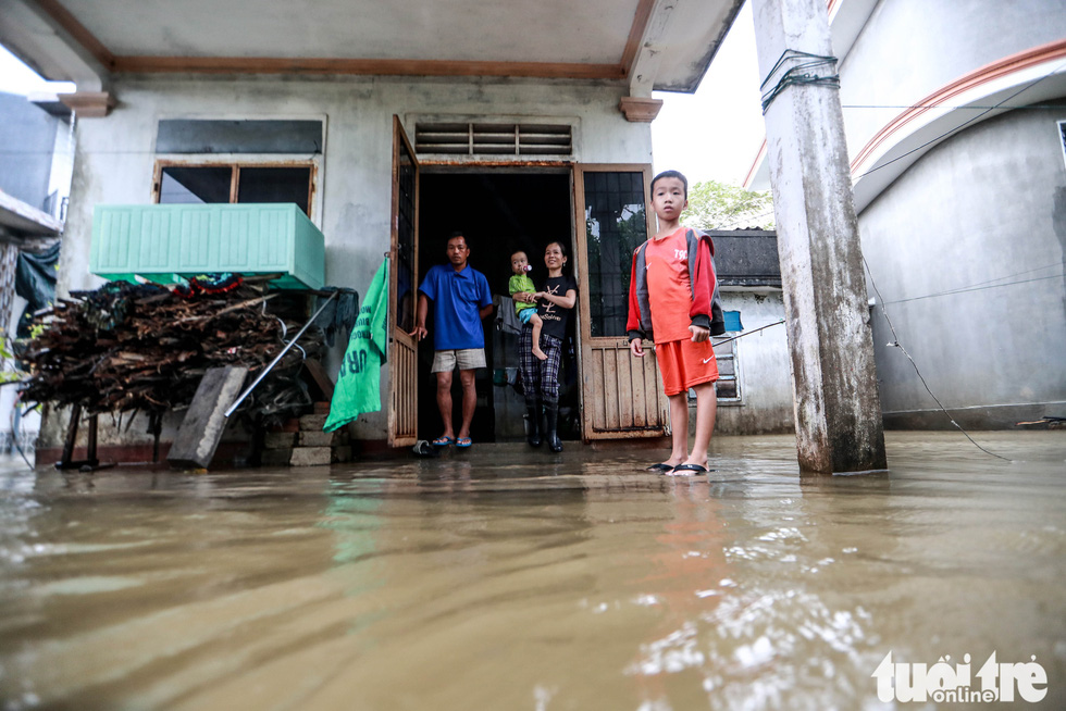 A family stand in front of their house in flooded Quang Phuoc Commune, Quang Dien District, Thua Thien-Hue Province on October 16, 2020. Photo: Nguyen Khanh / Tuoi Tre
