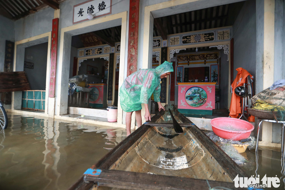 Local man Truong Dinh Cuong ties his boat to a pole in front of his house in flooded Quang Phuoc Commune, Quang Dien District, Thua Thien-Hue Province on October 16, 2020. Photo: Nguyen Khanh / Tuoi Tre