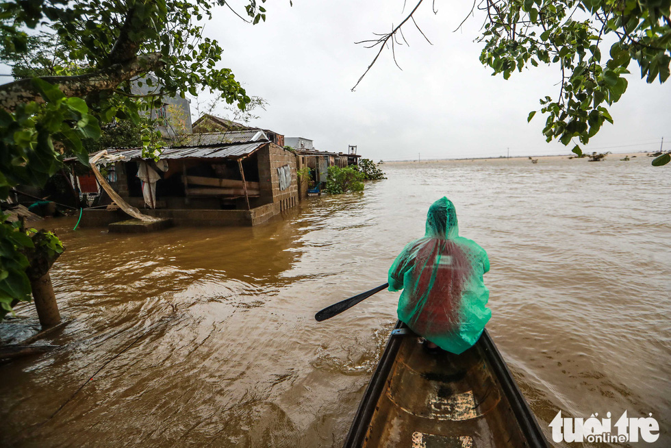 Local man Truong Dinh Cuong commutes on a boat in flooded Quang Phuoc Commune, Quang Dien District, Thua Thien-Hue Province on October 16, 2020. Photo: Nguyen Khanh / Tuoi Tre