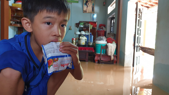 Phung Xuan Phuc, a child in Trieu Phong District of Quang Tri Province, eats raw instant noodles in his flooded house. Photo: Quoc Nam / Tuoi Tre