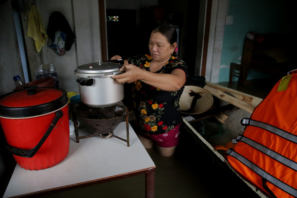 Ly Thi Le Thao cooks in her flooded house. Photo: Doan Nhan / Tuoi Tre