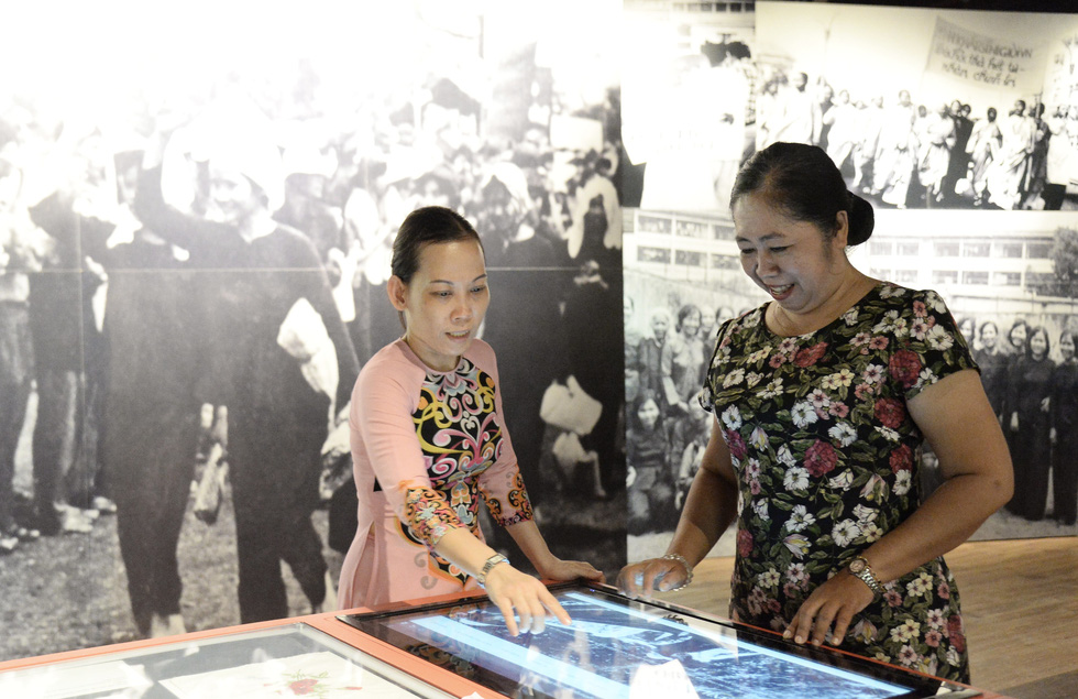 Two women use a touchscreen to access information at the Southern Women's Museum. Photo: Tu Trung / Tuoi Tre