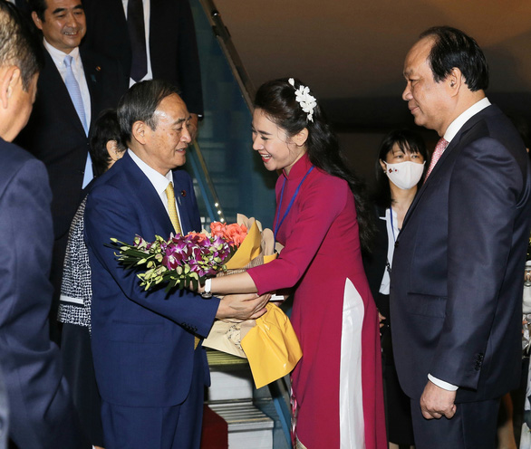 A Vietnamese woman gives flowers to Japanese Prime Minister Yoshihide Suga at Noi Bai International Airport in Hanoi, Vietnam, October 18, 2020. Photo: Vietnam News Agency