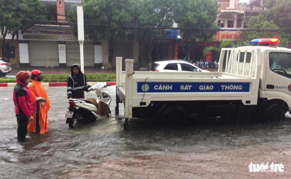 Traffic police of Ha Tinh City help residents to move a motorbike with breakdown on a flooded road. Photo: Quy Ngoc / Tuoi Tre