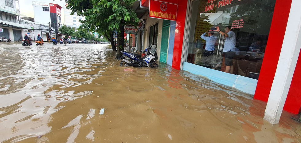 People are trapped by rising water inside a store on a street in Can Tho City, Vietnam, October 19, 2020. Photo: Chi Quoc / Tuoi Tre
