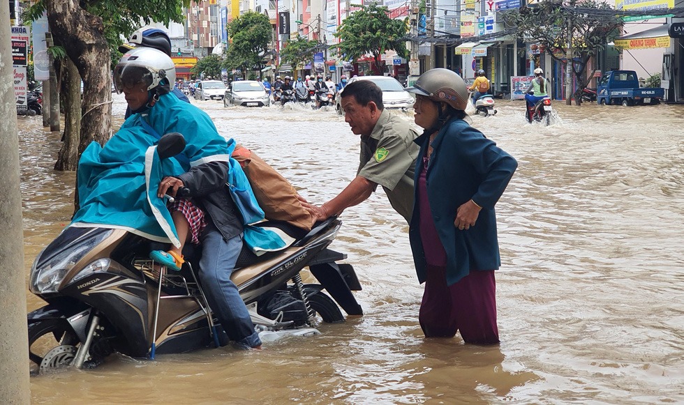 A man helps another man taking his child to school push his scooter through a flooded street to school in Can Tho City, Vietnam, October 19, 2020. Photo: Chi Cong / Tuoi Tre