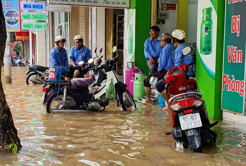 Deliverymen are trapped by rising water in front of a store on a street in Can Tho City, Vietnam, October 19, 2020. Photo: Chi Quoc / Tuoi Tre