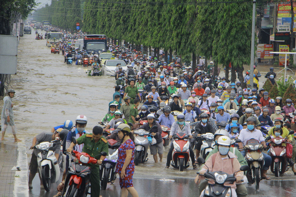 People wade through rising water on first day of week in Vietnam's Mekong Delta city