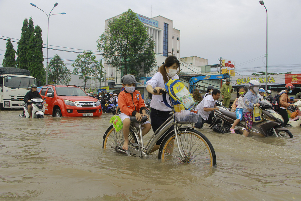 A woman walks a bicycle carrying her son through a flooded street to school in Can Tho City, Vietnam, October 19, 2020. Photo: Chi Cong / Tuoi Tre