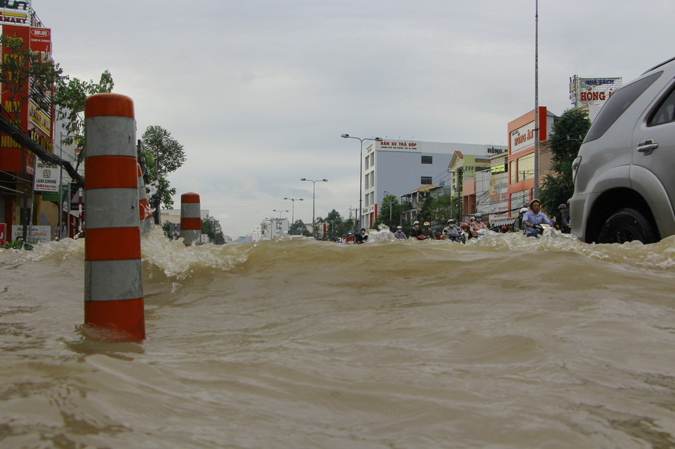 Rising water makes waves lash nearby vehicles on a street in Can Tho City, Vietnam, October 19, 2020. Photo: Chi Cong / Tuoi Tre