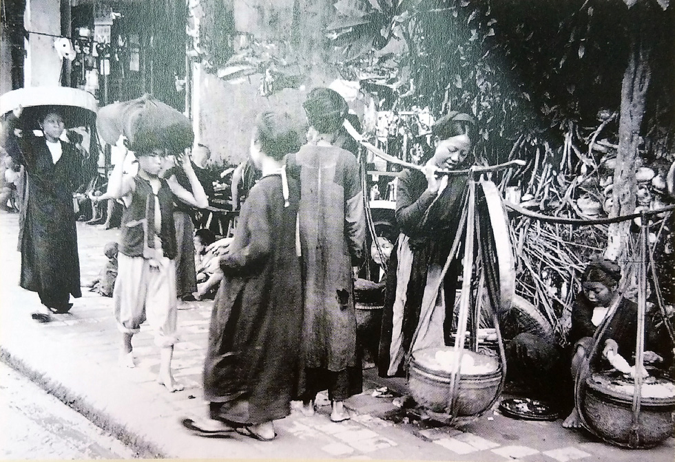 A photo depicts a street and passers-by in Hanoi, Vietnam prior to 1922.