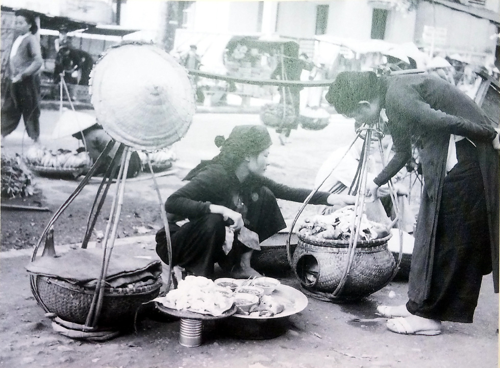 A photo features a peddler selling 'tiet canh long lon' (blood pudding), a popular local dish, on a street in Hanoi, Vietnam.