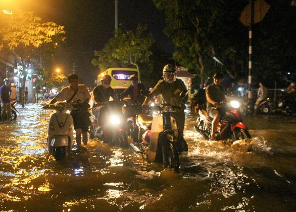 Commuters are seen walking their bike amidst floodwater in this photo taken in Ho Chi Minh City. Photo: Kim Ut / Tuoi Tre