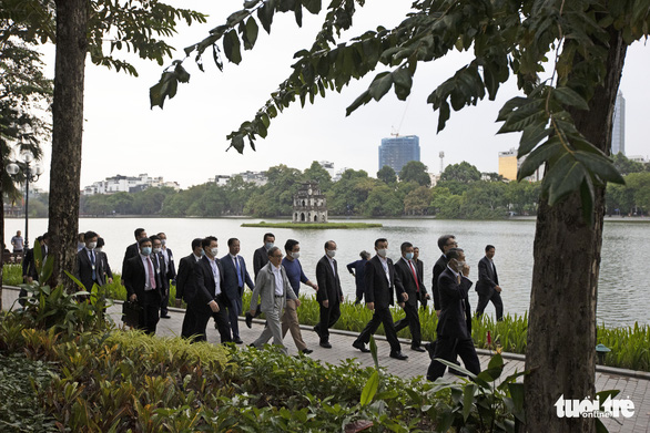 Japanese PM Suga walks with his entourage on the promenade of Hoan Kiem Lake in this photo taken on October 20. Photo: Viet Dung / Tuoi Tre
