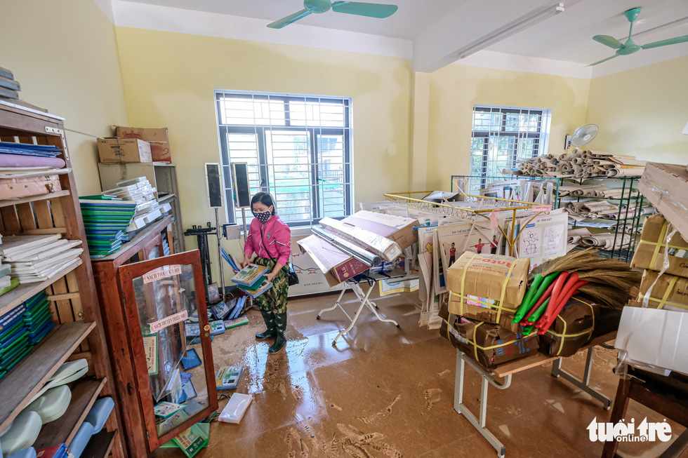 A teacher of Cam Quang Elementary School in Ha Tinh Province cleans up the school office after flooding. Photo: Nam Tran / Tuoi Tre
