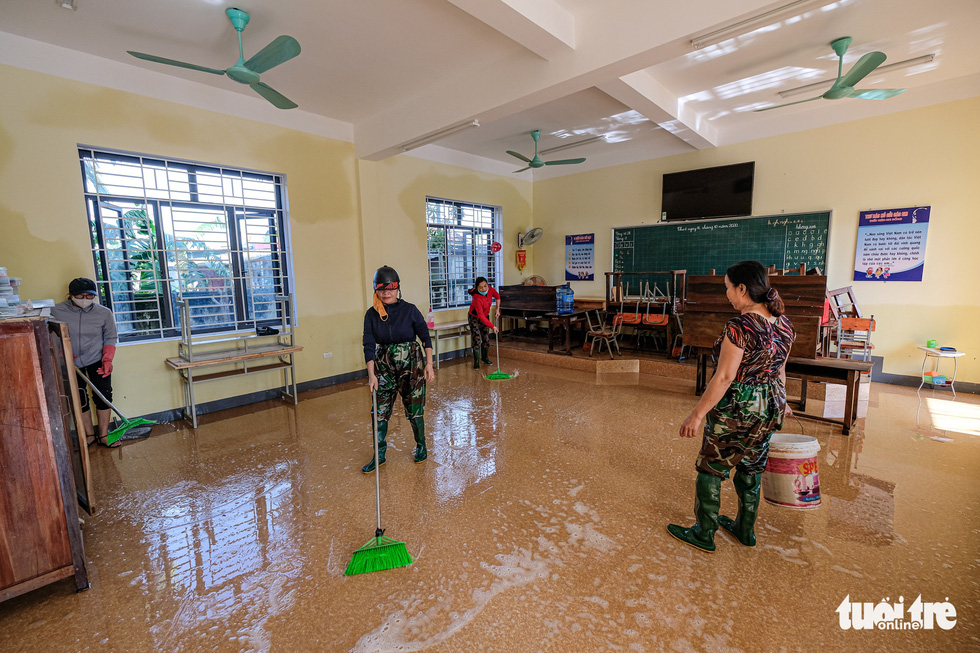 Teachers of Cam Xuyen District in Ha Tinh Province clean up a classroom of Cam Quang Elementary School. Photo: Nam Tran / Tuoi Tre