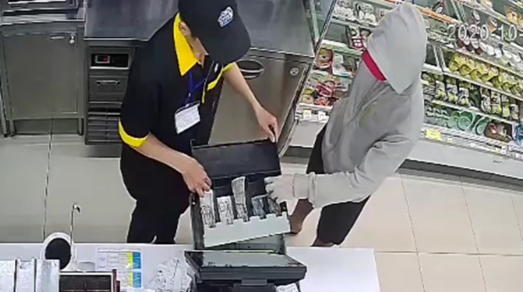 Pham Ngoc Anh Tuan takes money from the cashier's drawer inside a Ministop convenience store on Au Co Street, Tan Phu District, Ho Chi Minh City, October 12, 2020 in this screenshot taken from CCTV footage.