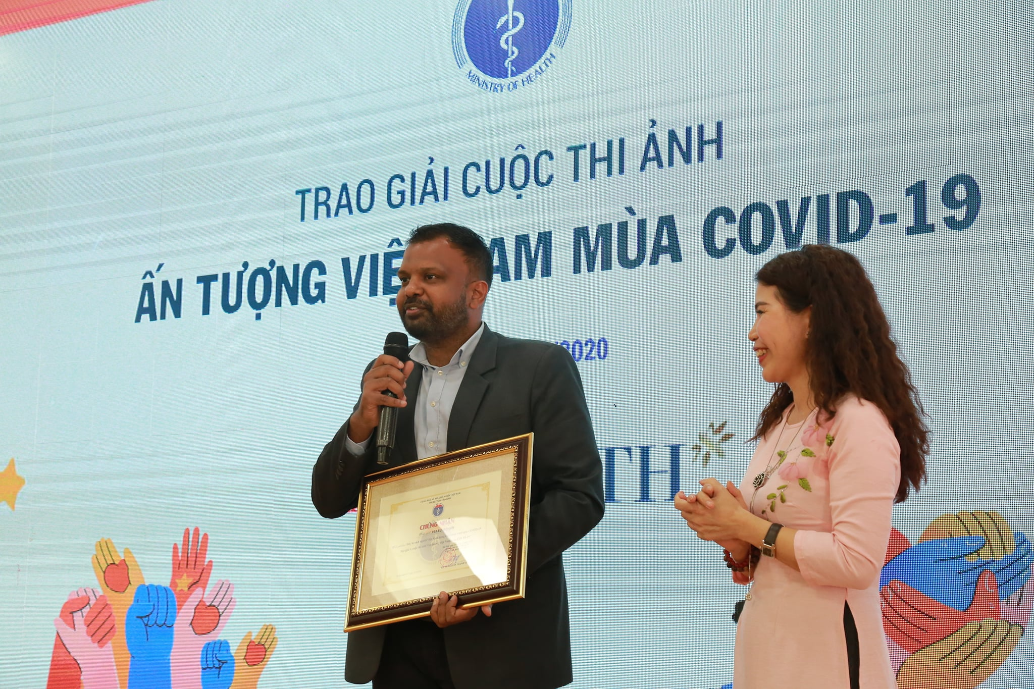 Prabu Mohan is seen receiving his award at the ceremony of a photo contest held by the Ministry of Health to celebrate Vietnam's impression during COVID-19 on October 23, 2020 in Hanoi in this photo published on the ministry's website.