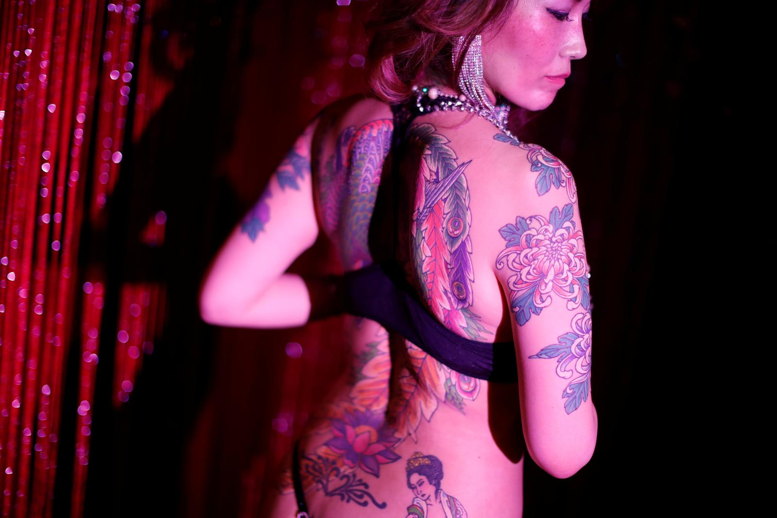 Burlesque dancer Aya Yumiko, 40, who performs under the stage name 'Aya Mermaid' poses with her tattoos at a bar she performs at in Tokyo, Japan, April 25, 2020. Photo: Reuters