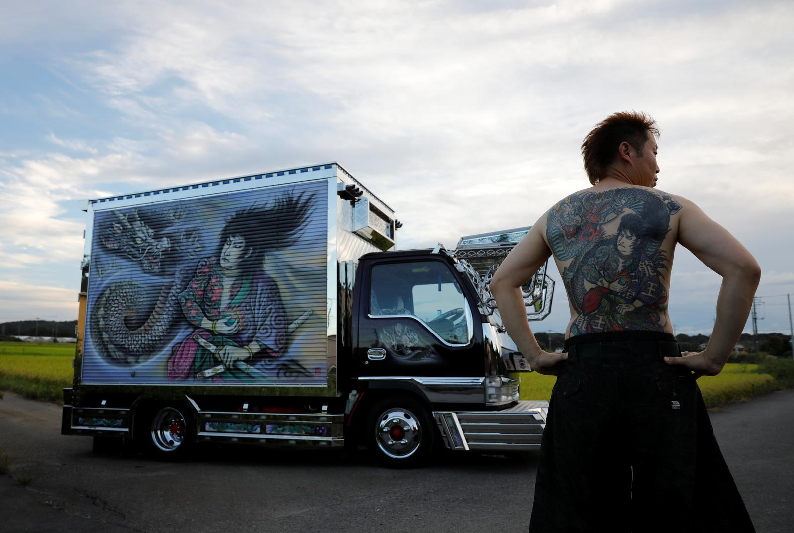 Truck driver Hideyuki Haga, 44, poses in front of his truck which is decorated with the same design as his tattoo on his back, in Hiki, Saitama, Japan, September 3, 2020. Photo: Reuters