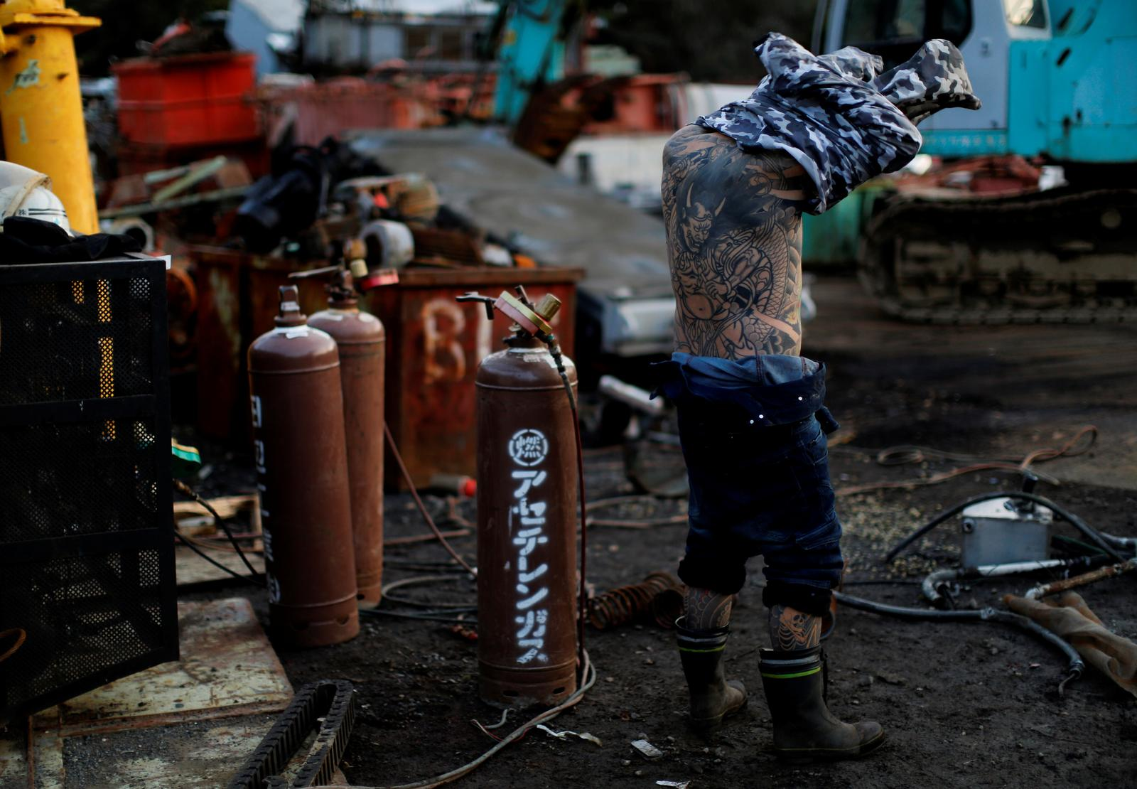 Scrap yard worker Hiroyuki Nemoto, 48, takes off his shirt as he gets ready to pose for a photo showing his tattoos at the scrap yard where he works in Hitachinaka, Ibaraki Prefecture, Japan, January 10, 2020. Photo: Reuters