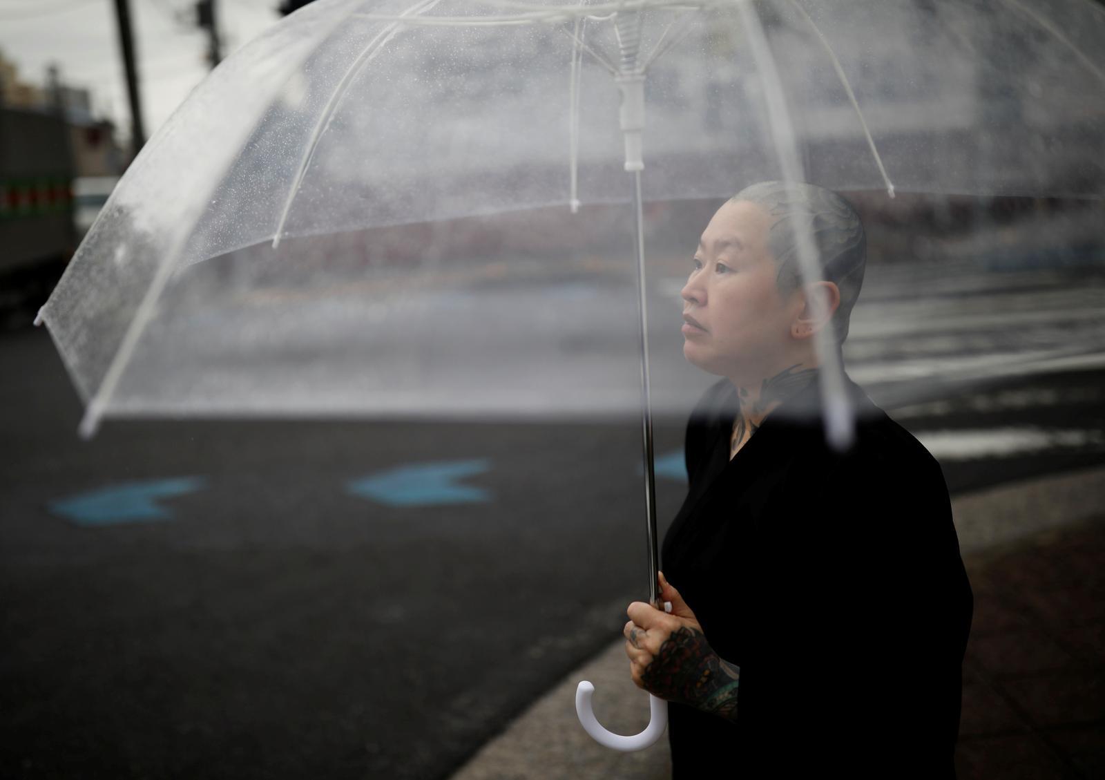Tattoo artist Shodai Horiren, 52, holds an umbrella as she walks in the rain in Warabi, Saitama Prefecture, Japan, July 3, 2020. Photo: Reuters