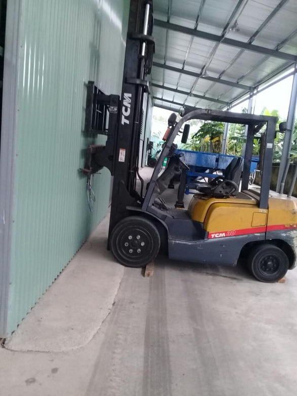A forklift is used to barricade the door of a building in Hoa Cam Industrial Zone of Da Nang City. Photo: Thu Trang / Tuoi Tre