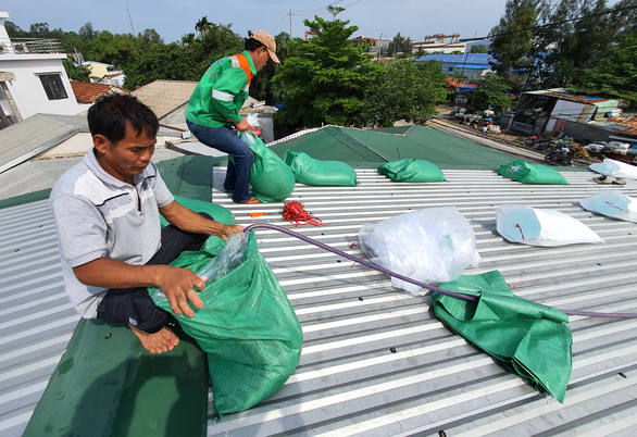 Residents of Binh Son District of Quang Ngai make water-filled bags to secure roofs. Photo: Phuoc Tuan / Tuoi Tre
