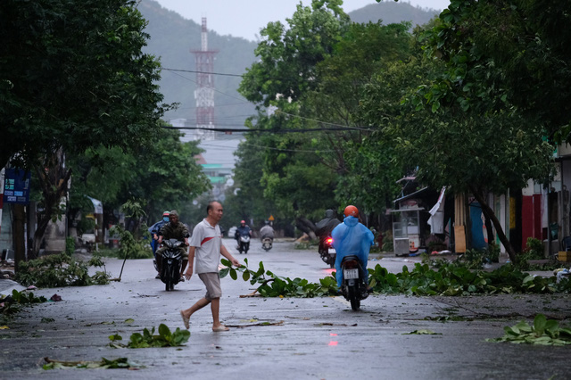 People travel on a street filled with tree branches in Quy Nhon City, Binh Dinh Province, Vietnam, October 28. 2020. Photo: M.Vinh / Tuoi Tre