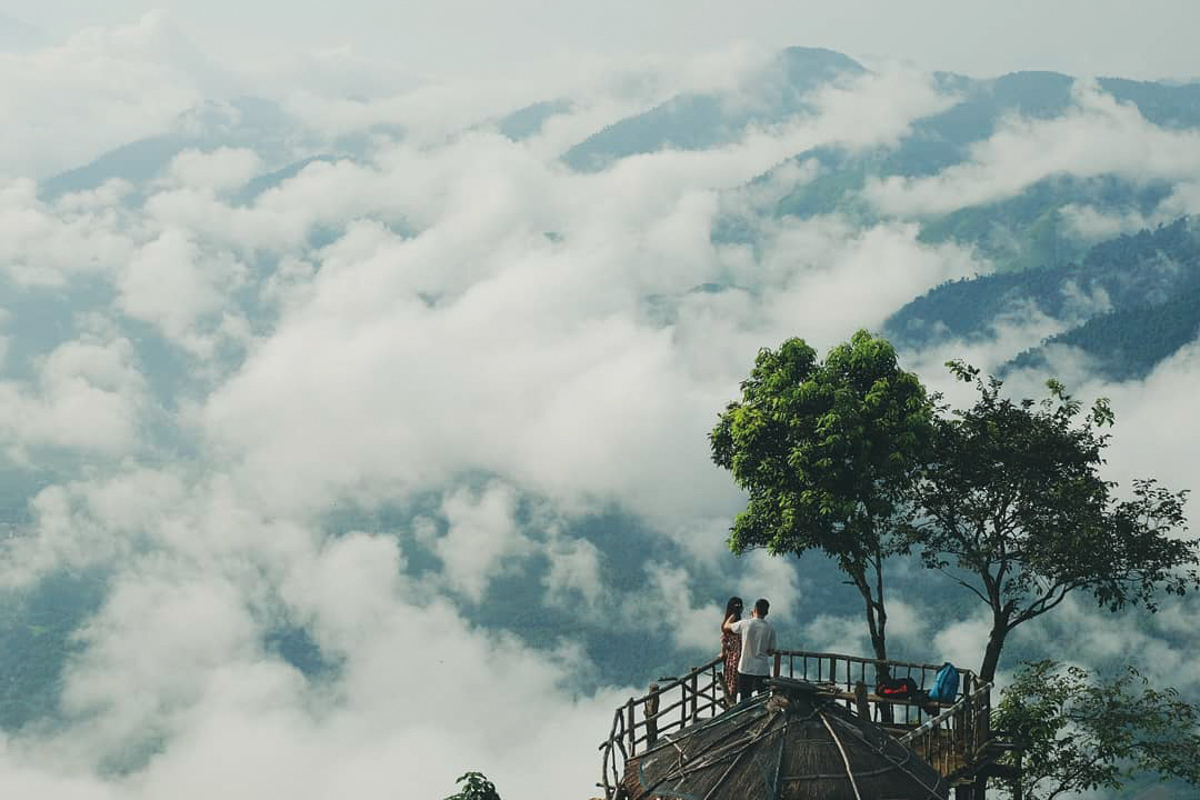 A couple take photos amid the imposing natural scene with mountains and clouds at Hang Kia Commune, Mai Chau District, Hoa Binh Province, Vietnam. Photo: Le Hong Thai / Tuoi Tre