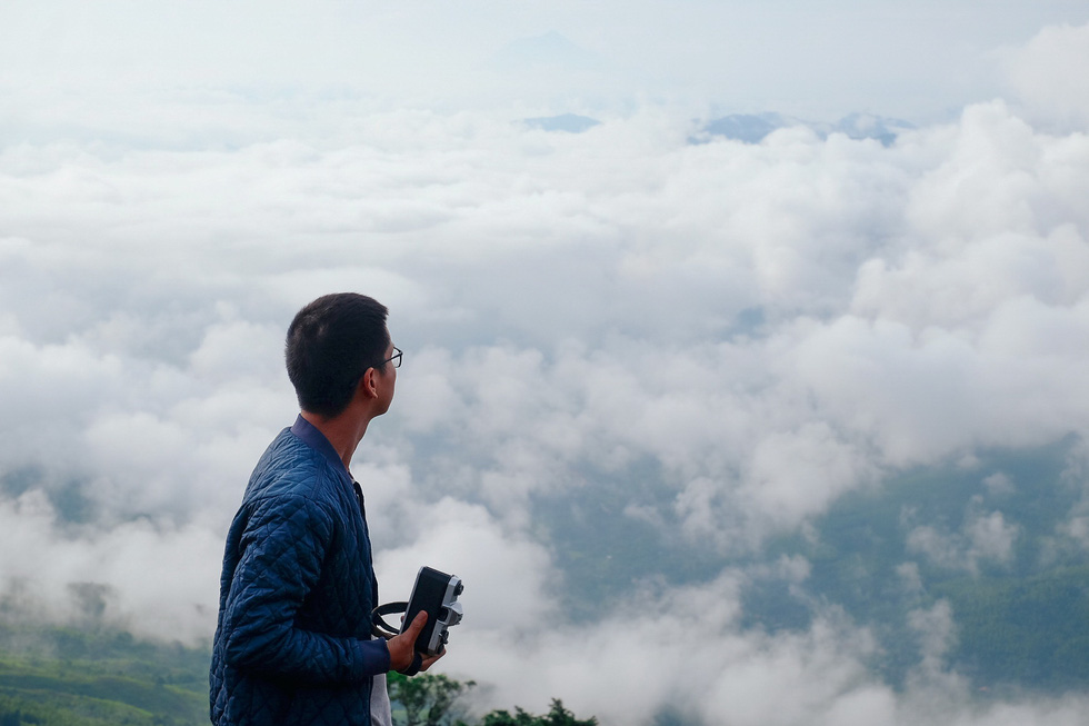 A tourist holds a camera to take pictures of the breathtaking scenery of mountains and clouds at Hang Kia Commune, Mai Chau District, Hoa Binh Province, Vietnam. Photo: Le Hong Thai / Tuoi Tre
