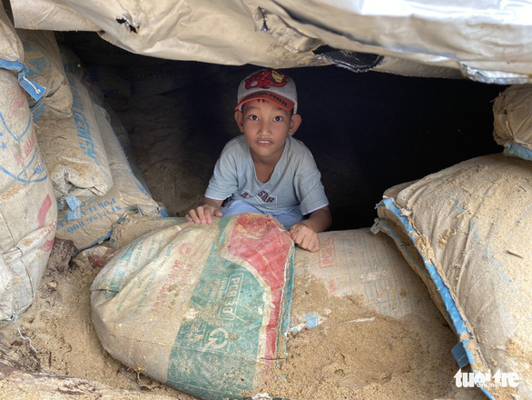 A child in seen hiding in a bunker made in preparation of Typhoon Molave in this photo taken In Quang Nam Province. Photo: Le Trung / Tuoi Tre